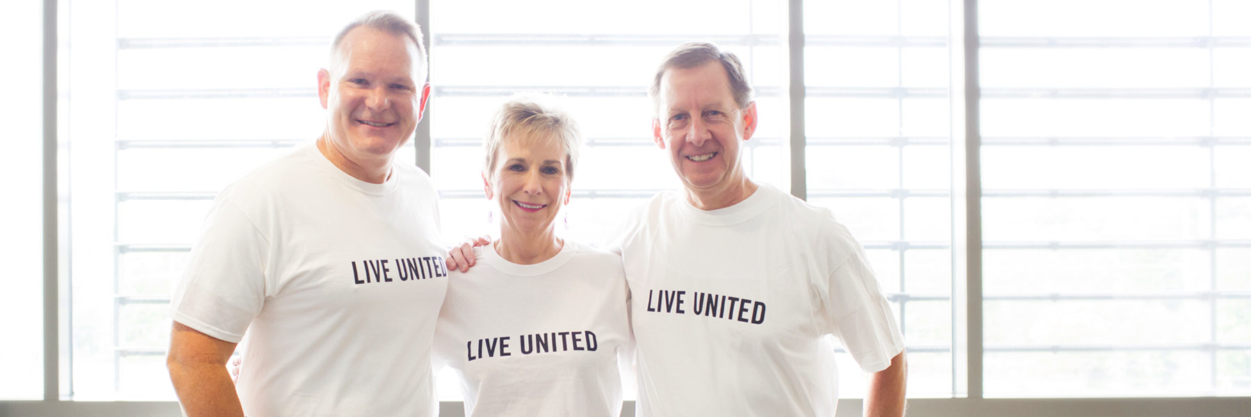 David Johnson, Deb Lemon, and Kirk White wearing T-shirts that say 'Live United'