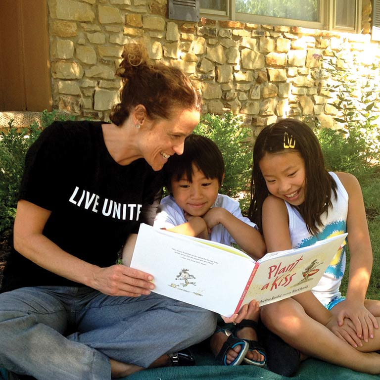 "A volunteer wearing a ""Live United"" T-shirt reads a picture book to two smiling children."