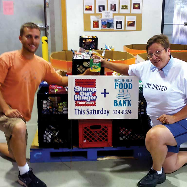 Two people kneel near food collected during the annual postal workers' food drive.
