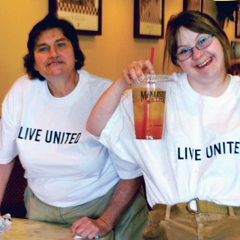 People wearing 'Live United' t-shirts smile for the camera.