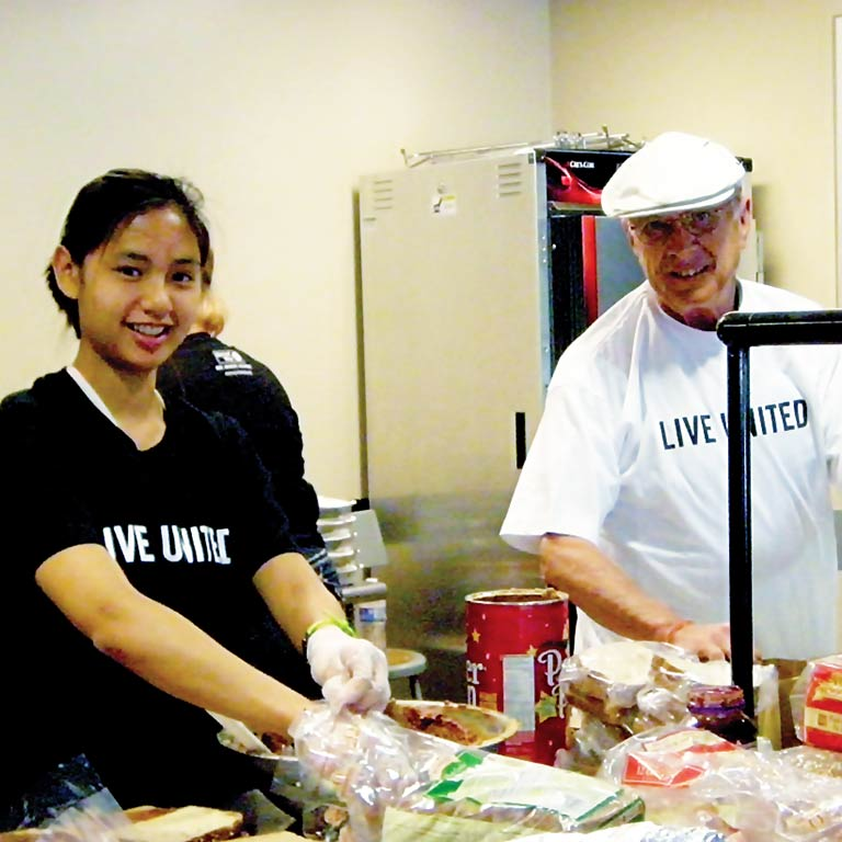 Volunteers wearing 'Live United' T-shirts make sandwiches.