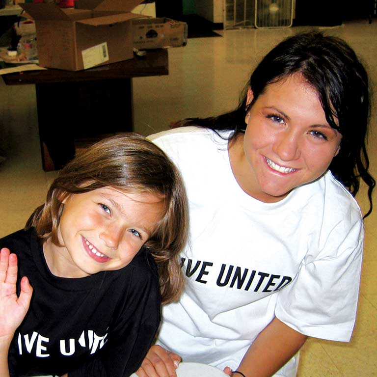 A woman and child, both wearing 'Live United' T-shirts, smile for the camera.