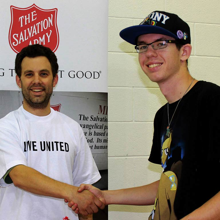 A man wearing a 'Live United' T-shirt shakes hands with a young man under a Salvation Army sign.