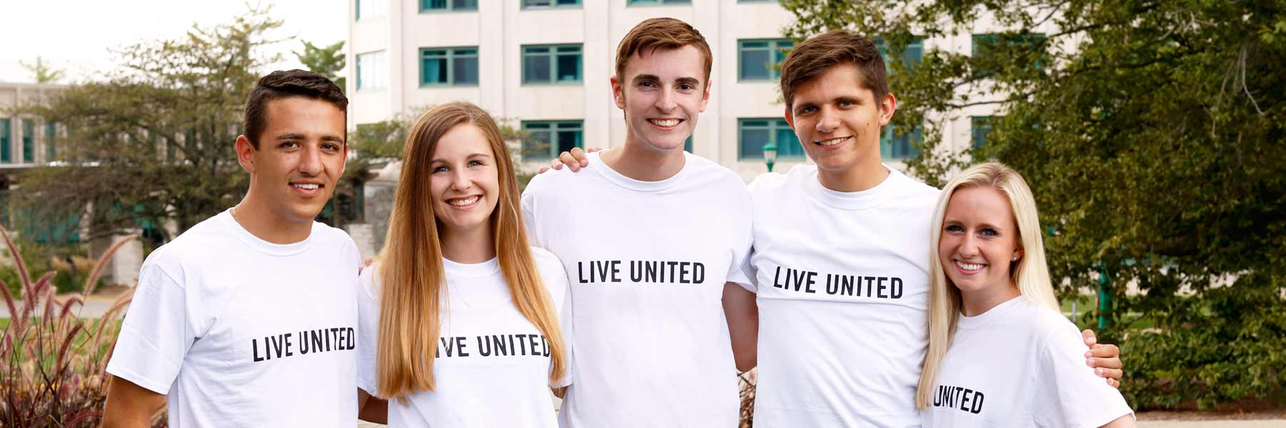 A group of young men and women, all wearing 'Live United' T-shirts, smile with their arms around each other.